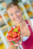 Supermarket worker holding strawberries Stock Image