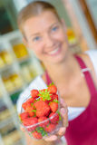 Supermarket worker holding strawberries Royalty Free Stock Photos