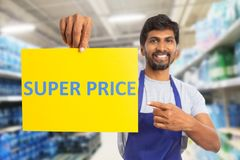 Supermarket worker pointing at super price paper. Male indian supermarket or hypermarket worker pointing with index finger at super price text on yellow paper as stock photography