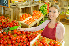 Supermarket worker by vegetables. Supermarket worker by the vegetables Royalty Free Stock Photo