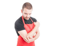 Supermarket young employee having elbow inflammation. As rheumatism concept isolated on white background royalty free stock photography
