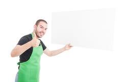Supermarketa sprzedawca pokazuje kciuk up i trzyma dużą reklamę Fotografia Stock