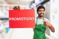 Supermarketanställd som rymmer befordringar, smsar på papper royaltyfri fotografi