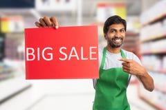 Supermarketanställd som rymmer stort försäljningspapper royaltyfri fotografi