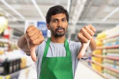 Supermarketarbetare som gör dubbel tumme-nergest arkivfoto