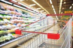 Supermarketlivsmedelsbutik med inre defocused bakgrund för frukt- och grönsakhyllor med den tomma shoppa vagnen arkivfoto