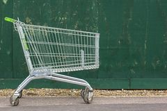 Supermarketsp?rvagn p? bakgrunden av ett gr?nt staket Supermarketvagn p? trottoaren royaltyfri foto