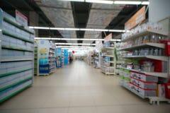 Supermarkt verwischte Hintergrund mit bunten Regalen und unerkennbaren Kunden Stockfotografie