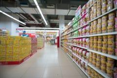 Supermarkt verwischte Hintergrund mit bunten Regalen und unerkennbaren Kunden Stockbild