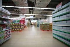 Supermarkt verwischte Hintergrund mit bunten Regalen und unerkennbaren Kunden Stockfotos