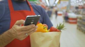 Supermarktangestellter, der Handy verwendet und Einkaufstasche im Supermarkt hält stock footage