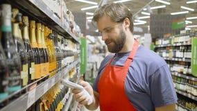 Supermarktangestellter im roten aport Scannenbarcode am Weinabschnitt im Supermarkt stock footage