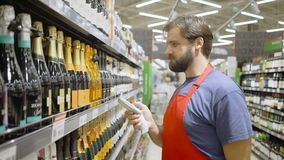 Supermarktangestellter im roten aport Scannenbarcode am Weinabschnitt im Supermarkt stock video