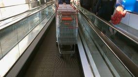 Supermarktarbeitskraft hebt auf Rolltreppe an und trägt viele Warenwagen stock video footage