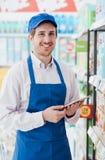 Supermarktbediende die een tablet gebruiken stock foto