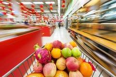 Supermarktbinnenland, met fruit van boodschappenwagentje wordt gevuld dat Stock Afbeeldingen