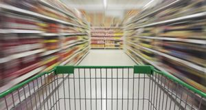 Supermarktdoorgang met leeg boodschappenwagentje Stock Foto's