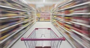 Supermarktdoorgang met leeg boodschappenwagentje Stock Afbeelding
