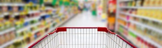 Supermarktdoorgang met leeg rood boodschappenwagentje royalty-vrije stock foto