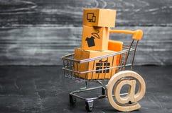 Supermarktkar met dozen, koopwaar: het concept het kopen van en het verkopen van goederen en diensten, Internet-handel die, onlin stock afbeelding