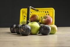 Supermarktkorb gefüllt mit Pflaumen und Äpfeln Stockfotografie
