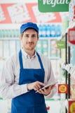 Supermarktsekretär unter Verwendung einer Tablette lizenzfreie stockbilder