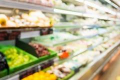 Supermarktspeicher mit Obst und Gemüse auf Regalen verwischte Hintergrund Stockfotografie