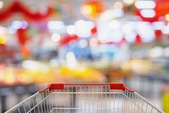 Supermarktspeicher-Unschärfehintergrund mit Warenkorb stockfotos