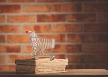 Supermarktwarenkorb und alte Bücher Stockbild