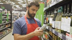 Supermarktwerknemer in de rode streepjescode van het aportaftasten bij wijnsectie in supermarkt stock video