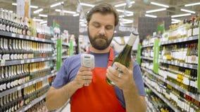 Supermarktwerknemer in rode de flessenstreepjescode van het aportaftasten bij wijnsectie in supermarkt stock videobeelden