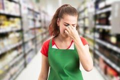 Supermarktwerknemer wat betreft neus met vingers royalty-vrije stock afbeeldingen