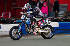 Supermato rider. OSWESTRY, UK - APRIL 27: An unnamed rider competing in the NoraSport UK Supermoto championship accelerates along a straight track section at the Royalty Free Stock Photo