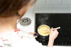 Supermom preparing dinner for a baby in a white modern kitchen stock photography