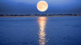 Supermoon rising over river stock video footage