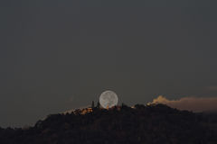 Supermoon setting over Buddhist temple on mountain Royalty Free Stock Images