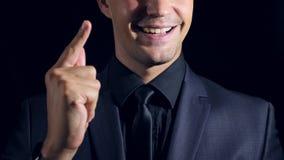 Supernahaufnahme eines Mannes in der schwarzen Kleidung auf einem schwarzen Hintergrund 4K Langsame Bewegung bemannen Sie Klicken stock video footage