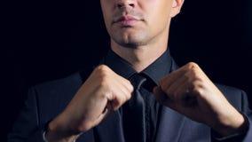 Supernahaufnahme eines Mannes in der schwarzen Kleidung auf einem schwarzen Hintergrund 4K Langsame Bewegung Manntänze stock video footage