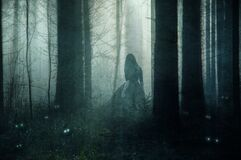 A supernatural concept of a ghostly woman wearing a long dress, walking through a spooky, foggy forest in winter. Surrounded by