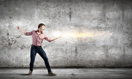Supernormal man. Young man in casual throwing light splashes stock images