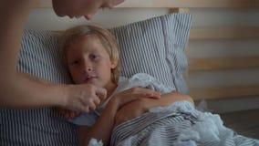 Superslowmotion在床上射击了一个病的小男孩 母亲测量他的温度并且亲吻他 婴孩流感概念 股票视频