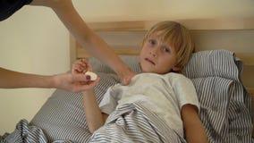 Superslowmotion在床上射击了一个病的小男孩 母亲用与精油的软膏摩擦男孩的胸口 婴孩流感 影视素材