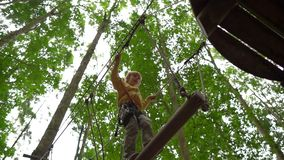 Superslowmotion在树梢的一条路线射击了安全带的一个小男孩上升在森林冒险公园 ? 股票视频