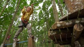 Superslowmotion在树梢的一条路线射击了安全带的一个小男孩上升在森林冒险公园 ? 股票录像