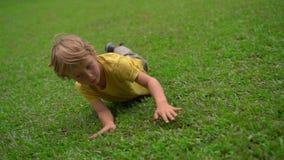 Superslowmotion射击了两个小男孩获得在草坪的乐趣 他们滚动下来小山 股票录像