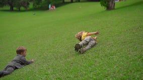 Superslowmotion射击了两个小男孩获得在草坪的乐趣 他们滚动下来小山 影视素材