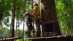 Superslowmotion射击了安全带攀登的两个小男孩在树梢的一条路线在森林冒险公园 影视素材