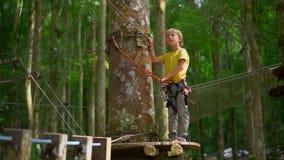 Superslowmotion射击了安全带的一个小男孩在一条路线在森林冒险公园 室外娱乐中心 股票录像