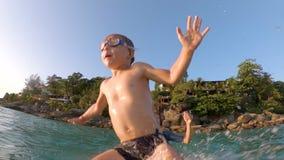 Superslowmotion сняло молодого отца throuing его маленький сын в море r Перемещение с концепцией детей видеоматериал