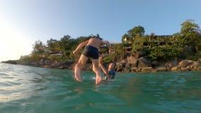Superslowmotion сняло молодого отца throuing его маленький сын в море r Перемещение с концепцией детей акции видеоматериалы